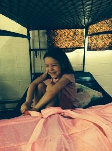 Elizabeth smiling in her cabin bunk bed.